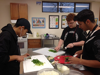 Charter College & Career Prep Students Bryan Jimenez, Elias Brown, and Alexander Camancho practice mincing in Culinary Arts class.