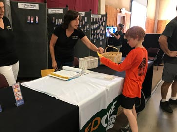 Student receives his taco ticket and prize at the Golden Star Student Award Booth at the 2018 El Dorado County Fair.