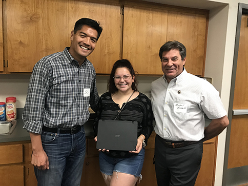 Dr. Ed Manansala and Supervisor Michael Ranalli present a new laptop to Sierra Rivera