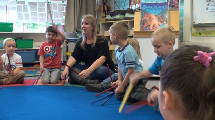 teacher sitting with small children on carpet as they tap the group with drumsticks