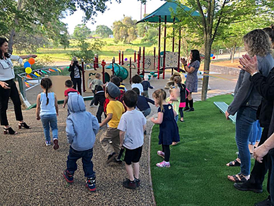 adults and children on playground at ribbon cutting
