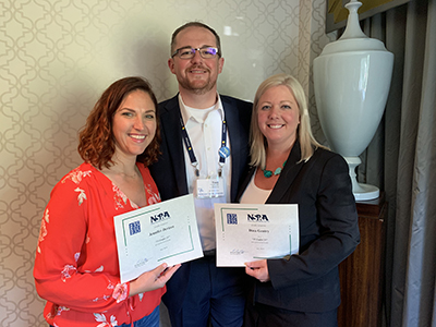 two women stand with awards with one man