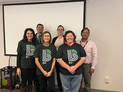 four adult women and two men standing together. Three of the adult women are wearing Big Brother Big Sisters tee shirts