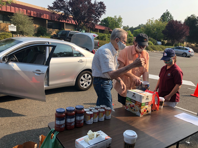 Kiwanis members organize donated food on table