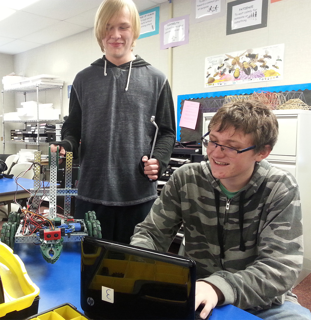 Charter Career Prep students Jace Young (junior) and Kalen Nelson (sophomore) collaboratively work on their robot.